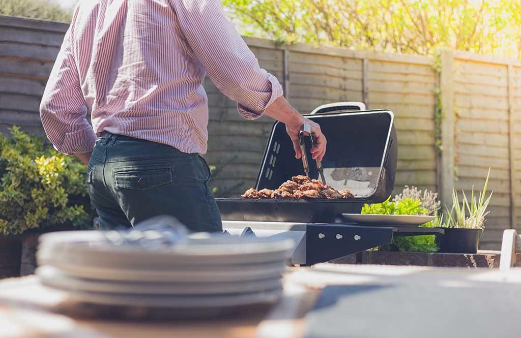 uomo che cuoce barbecue carne