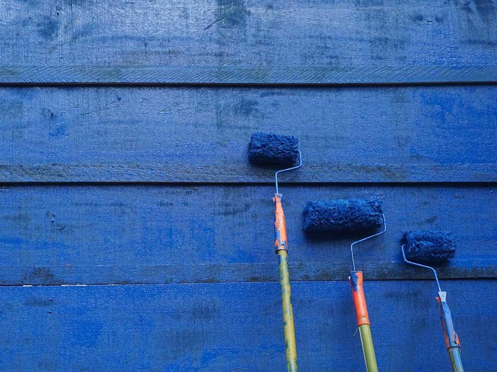 rulli vernice blu appoggiati alla parete