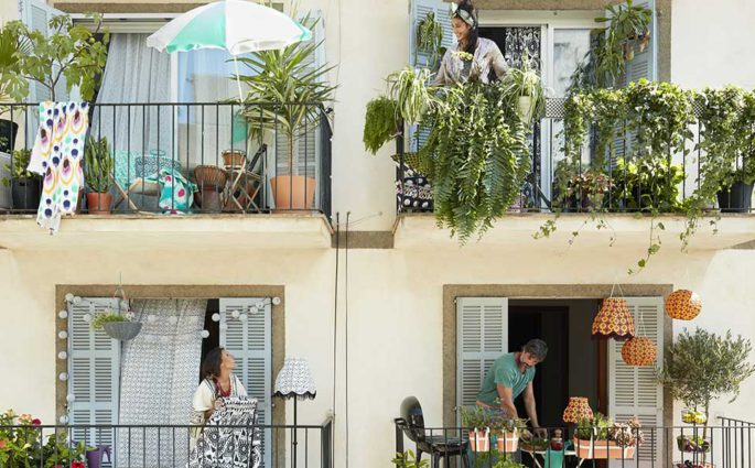 facciata palazzina con persone su balconi