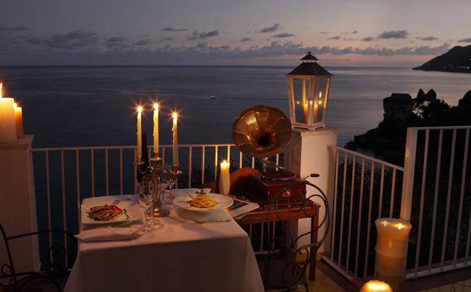 tavolo apparecchiato terrazza sul mare lume di candela