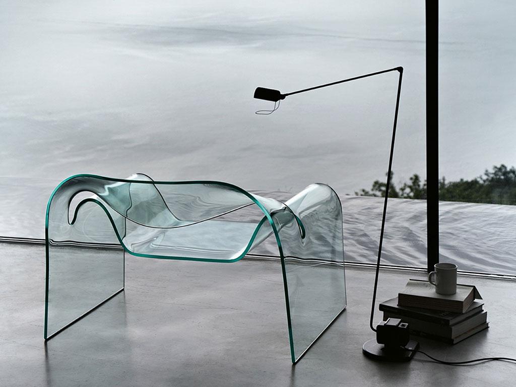 poltroncina in vetro ghost con accanto lampada da terra per lettura