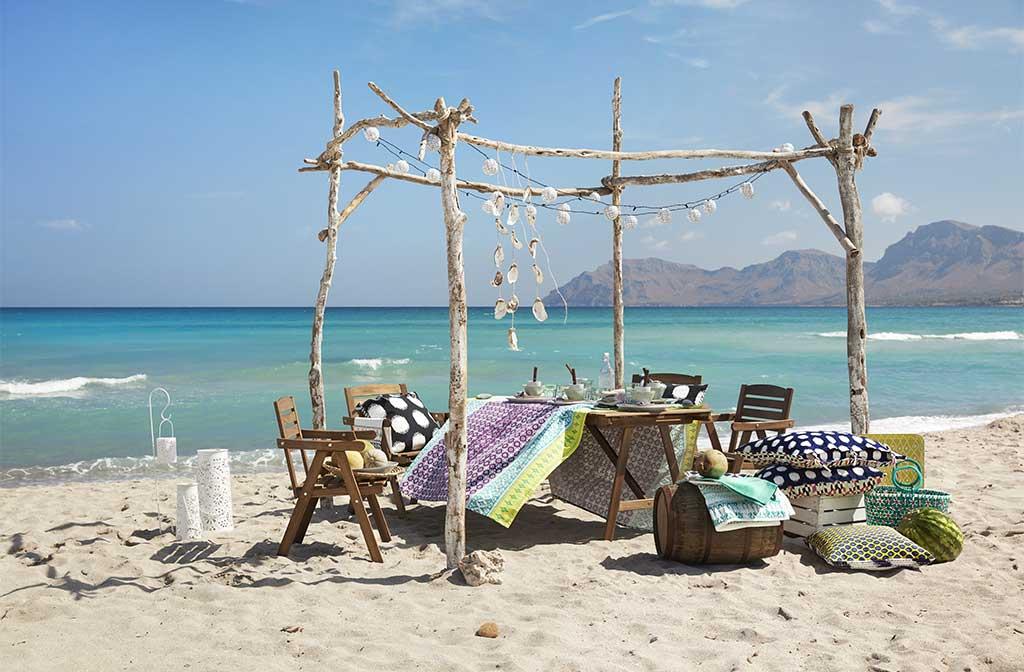 spiaggia sera tavola apparecchiata e sedie con cuscini