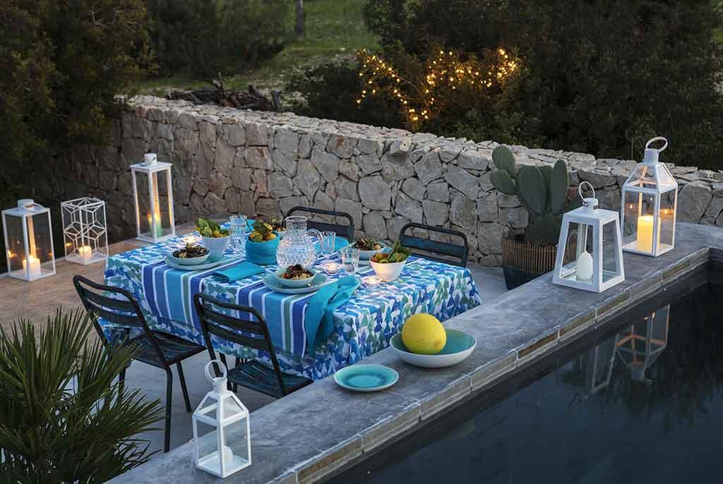 tavola apparecchiata in blu al tramonto in giardino