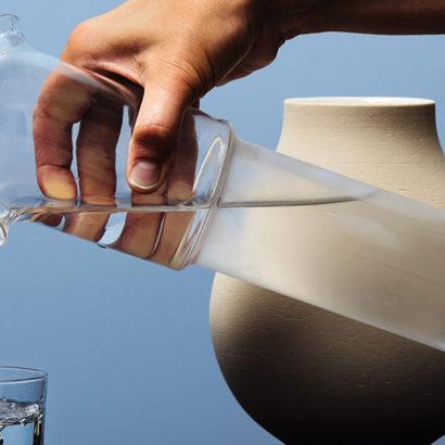 mano versa caraffa bottiglia vetro