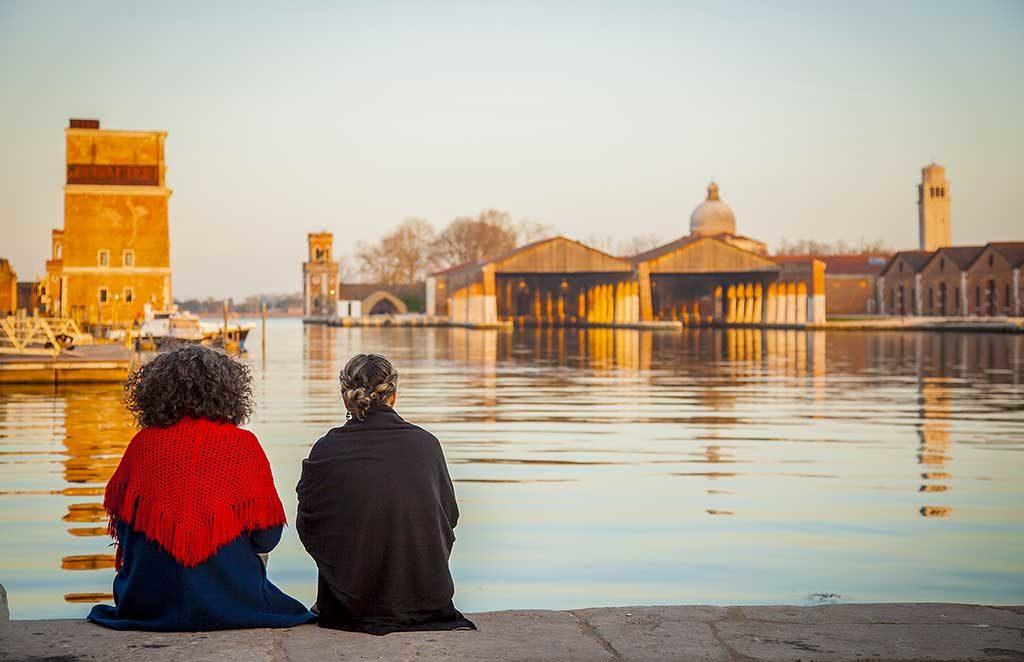 vista arsenale venezia persone sedute banchina