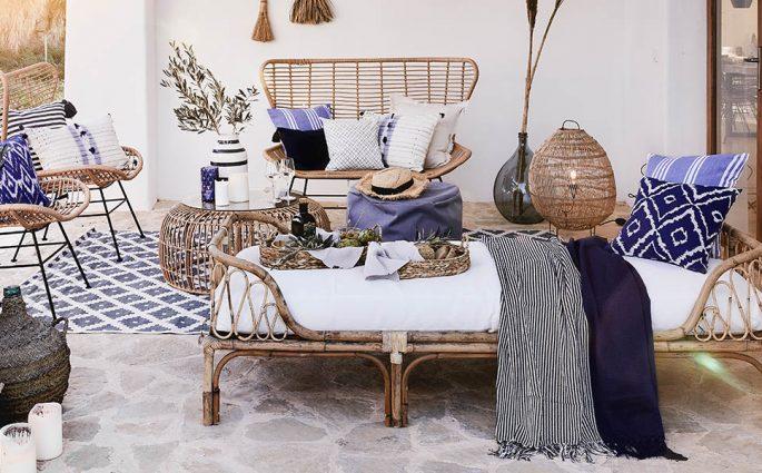 veranda con sedute intrecciate tappeto e cuscini