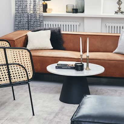 soggiorno con divano color ruggine e poltrona intrecciata
